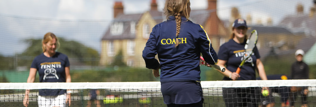 Adult coach at net with players