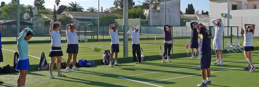Adults warm down and stretch after tennis