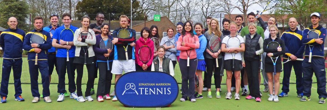 Adult tennis players and coaches at camp