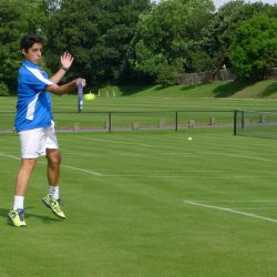 Tennis player hits forehand on a grass court